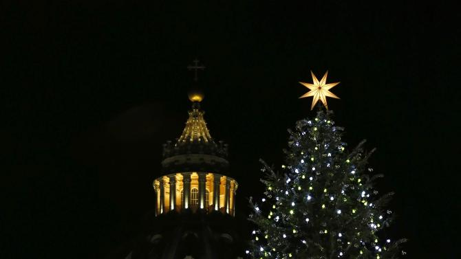 Saint Peter's Basilica and the Vatican Christmas tree are lit up after a ceremony in Saint Peter's Square at the Vatican