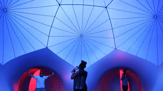 People walk through Exxopolis, an inflatable walk-in luminarium at Grand Park in Los Angeles, California