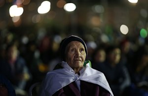 A woman watches a Stations of the Cross performance, …