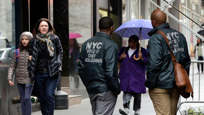 Members of the New York City Office of the Chief Medical Examiner stand on a sidewalk in Lower Manhattan Monday, April 29, 2013, near the place where a rusted metal part from the wing of a Boeing 767 was found wedged between a mosque and an apartment building on Friday, April 26. Investigators initially thought it was part of the landing gear, because both pieces have similar hydraulics. Authorities believe the aircraft part is from one of the two hijacked planes used in the Sept. 11 attacks on the nearby World Trade Center. The medical examiner's office said Monday it is preparing the site and plans to begin sifting for human remains in the area on Tuesday, April 30. (AP Photo/Richard Drew)