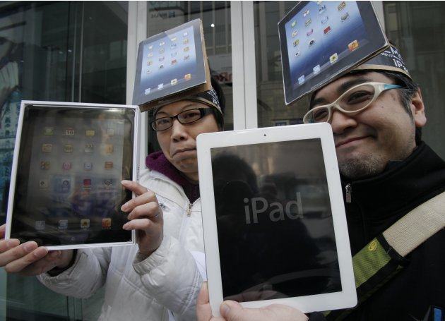 Japanese Ryota Musha, 41, right, and Hisanori Kogure, 31, show off new iPad tablet computers they purchased, in Tokyo Friday, March 16, 2012. Sales of the third version of Apple's iPad began Friday mo