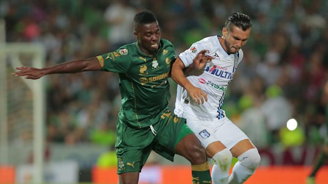 Santos' striker Djaniny Tavares battles for the ball with Yasser Corona of Queretaro during the first leg of their Mexican first division final soccer match at the TSM Corona stadium in Torreon