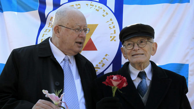 Survivor of Auschwitz  Moshe Haelion and Israel Ambassador Arye Mekel , left, hold flowers in the northern port city of Thessaloniki, Greece, on Saturday, March 16, 2013. Jewish residents in this northern Greek city have gathered to commemorate the 70th anniversary from the first roundup and deportation of Jews to Nazi extermination camps in World War II. By August 1943, 46,091 Jews had been deported to Auschwitz-Birkenau. Of those, 1,950 survived. (AP Photo/Nikolas Giakoumidis)