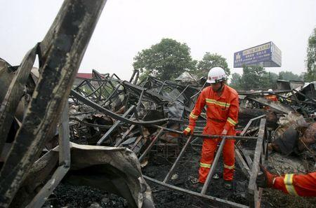 Firefighters clean up the debris after a fire at a rehabilitation centre for elderly in Sanlihe village of Pingdingshan