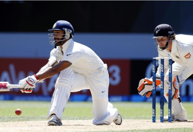 India's Shikhar Dhawan hits a reverse sweep watched by New Zealand's BJ Watling on his way to scoring a century during his second innings on day four of the first international test cricket ma