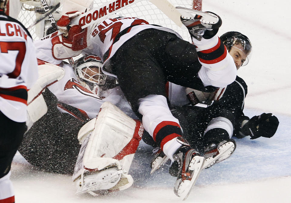 New Jersey Devils goalie Martin Brodeur (30), Bryce Salvador (24) and Los Angeles Kings center Trevor Lewis (22) fight for control of the puck in the third period during Game 4 of the NHL hockey Stanley Cup finals, Wednesday, June 6, 2012, in Los Angeles.  (AP Photo/Jae C. Hong)