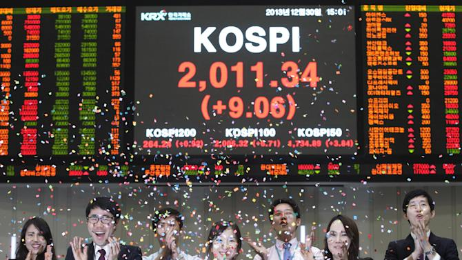 Staff members of the Korea Exchange applaud as they threw confetti for the media during the year's market closing ceremony near a screen showing the Korea Composite Stock Price Index (KOSPI) at the Korea Exchange in Seoul, South Korea, Monday, Dec. 30, 2013. The Korea Composite Stock Price Index closed the year's last trading at 2,011.34. (AP Photo/Ahn Young-joon)