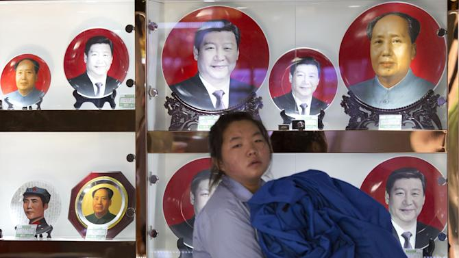 In this photo taken Wednesday, June 4, 2014, a sales person walks past commemorative plates featuring Chinese President Xi Jinping and former supreme leader Mao Zedong at a souvenir stall in Beijing, China. Xi's recent ouster of one of China's top military figure and forceful style of leadership had prompted suggestions he might be trying to roll back the consensus-oriented leadership of the past two decades and restore rule by a dominant strongman. But experts say collective leadership is here to stay because the ruling party is wary of returning to the turbulence China endured under the former supreme leader Mao Zedong. (AP Photo/Ng Han Guan)