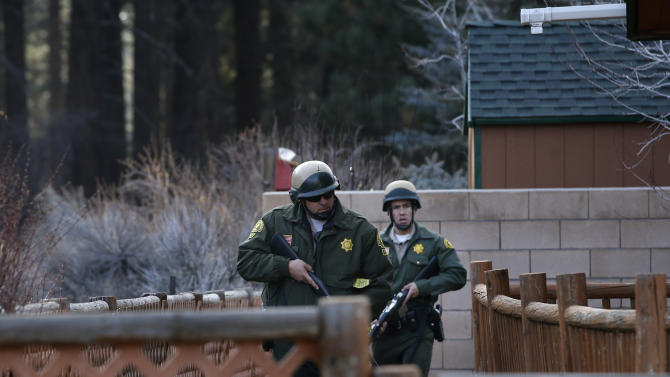 San Bernardino County sheriff's deputies search a home during a manhunt for former Los Angeles officer Christopher Dorner in Big Bear, Calif, Thursday, Feb. 7, 2013. The ex-Los Angeles police officer who authorities say went on a killing spree to punish those he blamed for his firing killed three people, set off a manhunt that stretched across three states and into Mexico, and stirred fear throughout the region. (AP Photo/Jae C. Hong)
