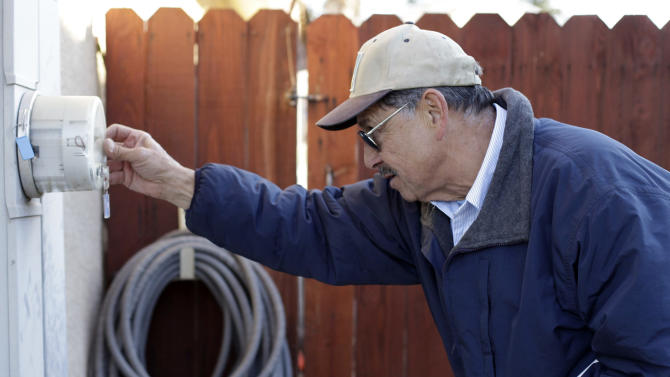 In this Friday, Jan. 11, 2013 photo, PG&E employee Art Liscano, 66, reads a meter at a house in Clovis, Calif. The number of meter readers in the U.S. fell from 48,000 in 2000 to 36,000 in 2010. Every day, PG&E  replaces 1,200 old-fashioned meters with digital versions that can collect information without human help, generate more accurate power bills, and even send an alert if the power goes out.  (AP Photo/Gosia Wozniacka)