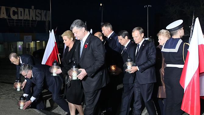 Foreign leaders taking part in a ceremony marking 70 years since the end of World War II, light candles at the monument to Gdansk shipyard workers killed by the security and the armed forces in 1970, in front of the shipyard in Gdansk, Poland, on Thursday, May 7, 2015. Present are U.N. Secretary General Ban Ki-moon, European Council President Donald Tusk, a native of nearby city of Gdansk, and the presidents of Ukraine and several Central European countries. Poland's President Bronislaw Komorowski meant the gathering as an alternative celebration to Moscow's Red Square parade scheduled for Saturday, at a time of deep divisions between the West and Russia, over Moscow's actions in Ukraine. (AP Photo/Czarek Sokolowski)