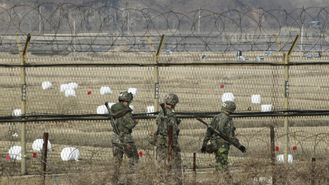 South Korean army soldiers patrol along a barbed-wire fence near the border village of Panmunjom in Paju, South Korea, Monday, April 8, 2013. South Korea's top security official said Sunday that North Korea may be setting the stage for a missile test or another provocative act with its warning that it soon will be unable to guarantee diplomats' safety in Pyongyang. But he added that the North's clearest objective is to extract concessions from Washington and Seoul. (AP Photo/Ahn Young-joon)