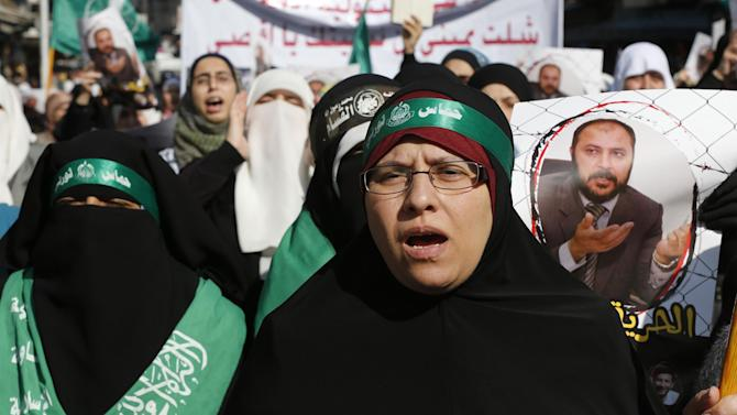 Protesters from the Islamic Action Front, carry picture of the deputy overall leader of Jordanian Muslim Brotherhood Rsheid, during a demonstration in Amman