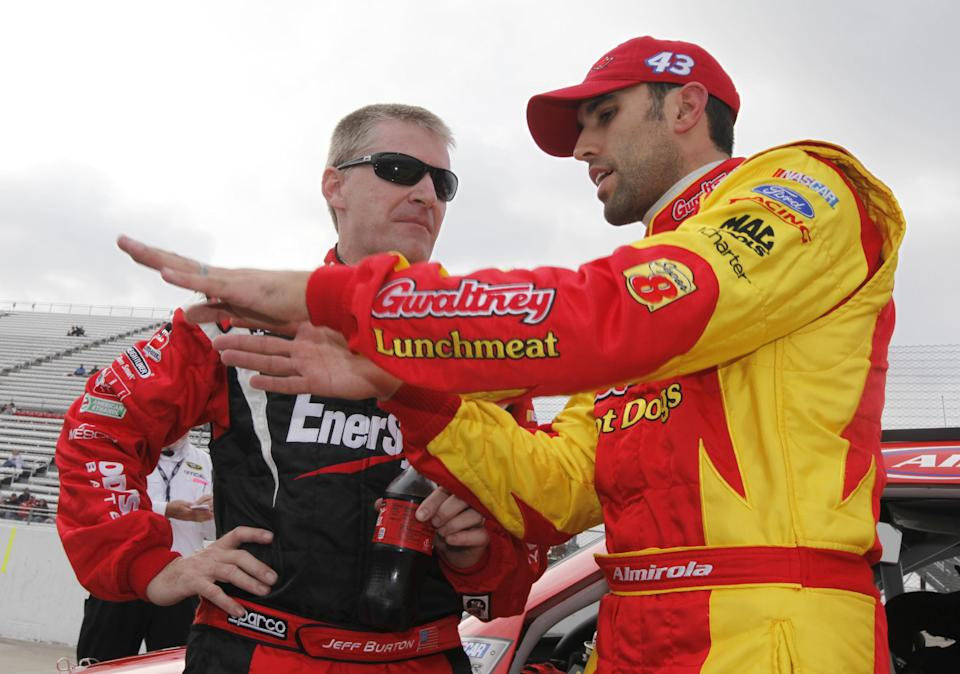 Jeff Burton, left, talks with Aric Almirola, right, during qualifying for Sunday's NASCAR Sprint Cup Series auto race at Martinsville Speedway in Martinsville, Va., Friday, Oct. 26, 2012. (AP Photo/Steve Helber)