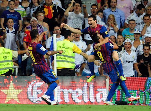 Barcelona's Argentinian forward Lionel Messi (up) celebrates with Barcelona's midfielder Thiago Alcantara (L) and Barcelona's Chiliean forward Alexis Sanchez (R)after scoring during the first leg of the Spanish Supercup football match Real Madrid against Barcelona at the Santiago Bernabeu stadium in Madrid on August 14, 2011. AFP PHOTO/ DANI POZO (Photo credit should read DANI POZO/AFP/Getty Images)