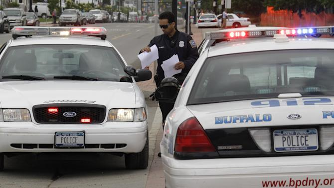 "Law enforcement officers hand out photos of a man to other officers at the scene of a shooting at Erie Count Medical Center in Buffalo, N.Y., Wednesday, June 13, 2012. A  police official confirms that a woman was killed Wednesday morning on the grounds of the Erie County Medical Center, which he describes as being in ""complete lockdown"" as SWAT teams and other officers cordon off the 65-acre campus.(AP Photo/David Duprey)"