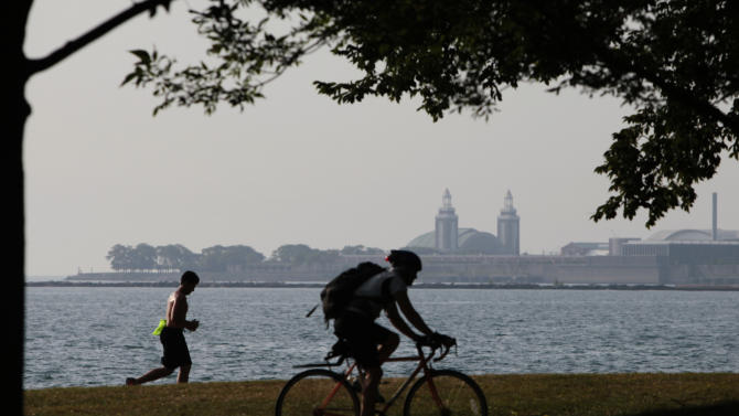 """An early morning cyclist and a jogger head to downtown along the shore of Lake Michigan Wednesday, July 20, 2011 in Chicago. Much of the United States is trapped under a heat """"dome"""" caused by a huge area of high pressure that's compressing hot, moist air beneath it, leading to miserable temperatures in the mid-90s to low 100s and heat-index levels well above 100 degrees. (AP Photo/Kiichiro Sato)"""