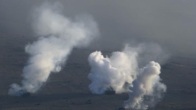 Georgian army tanks release smoke screens during a military drill at the Vaziani base outside Tbilisi