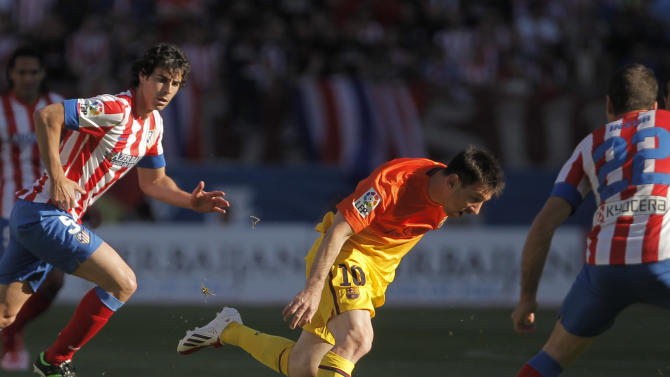 FC Barcelona's Lionel Messi from Argentina, center, in action with Atletico de Madrid's Tiago Mendes from Portugal, left, during a Spanish La Liga soccer match at the Vicente Calderon stadium in Madrid, Spain, Sunday, May 12, 2013. (AP Photo/Andres Kudacki)