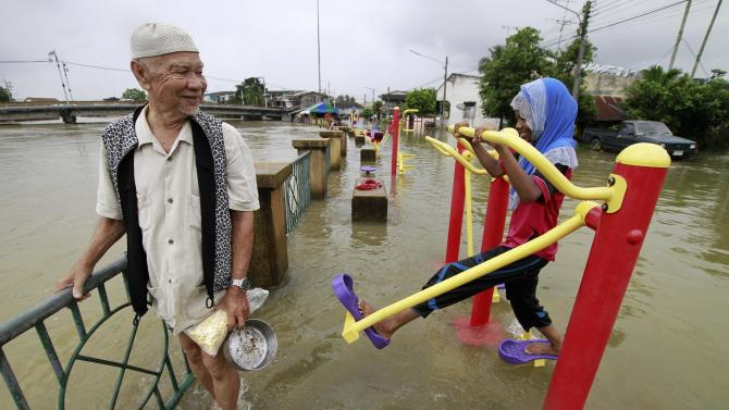 Man wades through a flooded street as a girl uses an exercise machine in the Pattani province
