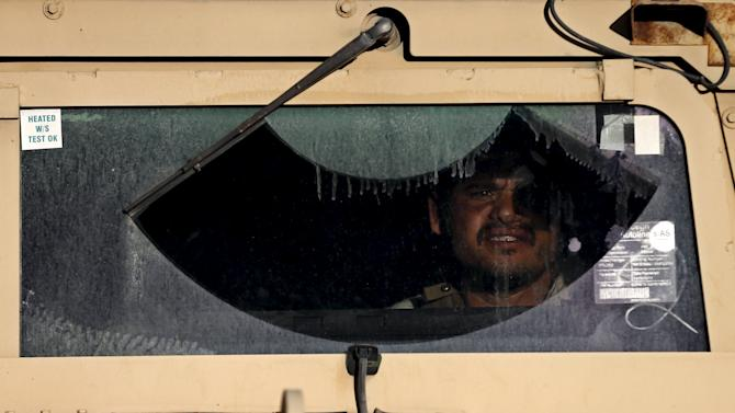 Afghan security force looks out from the windshield of an armoured car at the site of an attack in Kabul