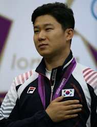 Gold medallist South Korean Jin Jongoh listens to the playing of his national anthem during the podium ceremony for the 10m Air Rifle Men final at the Royal Artillery Barracks in London on July 28, 2012, during The London 2012 Olkympic Games. AFP PHOTO/MARWAN NAAMANI