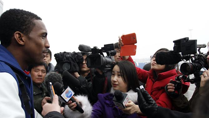 "Bull Bullard, left, a member of the Harlem Globetrotters, is mobbed by journalists upon arrival at Pyongyang Airport, North Korea, Tuesday, Feb. 26, 2013. Flamboyant former NBA star Dennis Rodman known as ""The Worm"" arrived with three members of the basketball team, a VICE correspondent and a production crew from the company in Pyongyang, becoming an unlikely ambassador for sports diplomacy at a time of heightened tensions between the U.S. and North Korea. (AP Photo/Kim Kwang Hyon)"