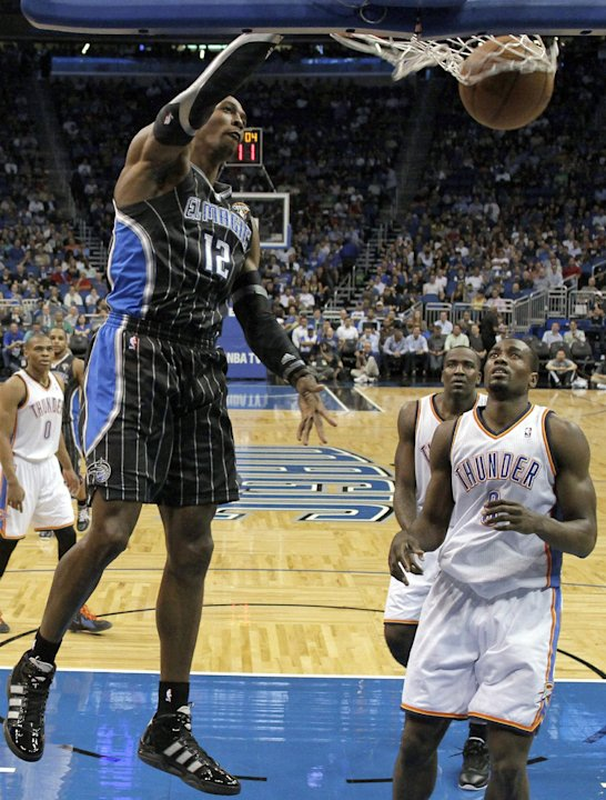 Orlando Magic's Dwight Howard (12) dunks the ball in front of Oklahoma City Thunder's Serge Ibaka during the first half of an NBA basketball game Thursday, March 1, 2012, in Orlando, Fla. (AP Photo/Jo