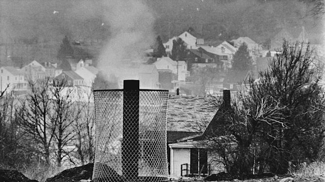FILE - In this Jan. 26, 1983, file photo, smoke rises from the ground in Centralia, Pa., where and uncontrolled underground mine fire was burning. The attorney for the few remaining residents of the central Pennsylvania coal town that was decimated by a 50-year-old mine fire said on Thursday, Oct. 31, 2013, that they have settled their lawsuit against state officials who have been trying for years to evict them. The settlement allows eight Centralia residents to stay in their homes for as long as they live and it also includes a cash payout. (AP Photo/Rusty Kennedy, File)