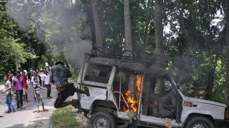 A demonstrator kicks a vehicle that was set on fire during a protest at Golaghat district in Assam