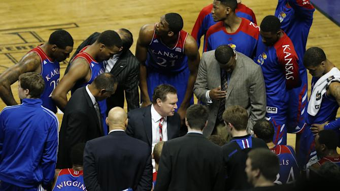 Kansas head coach Bill Self huddles with team during the second half of an NCAA college basketball game against Kansas State in Manhattan, Kan., Monday, Feb. 10, 2014. Kansas State defeated Kansas 85-82 in overtime