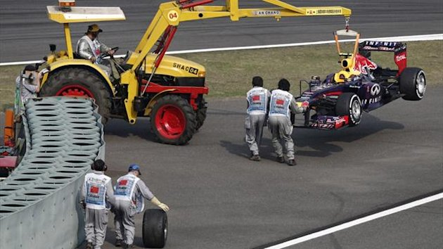Marshalls collect a wheel as they recover Red Bull Formula One driver Mark Webber of Australia's car during the Chinese F1 Grand Prix at the Shanghai International Circuit (Reuters)