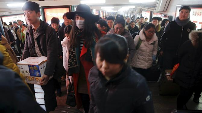 Passengers carry their belongings after arriving at the Beijing Railway Station during the Chinese Lunar New Year travel rush, as annual Spring Festival holidays end