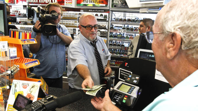 In this Nov. 29, 2012 file photo, television cameras rolling, as store manager Bob Chebat, middle, hands over Wes Prinzen's, right,  modest $4 winnings, at a 4 Sons Food Store where one of the winning tickets in the $579.9 million Powerball jackpot was purchased in Fountain Hills, Ariz.  When two winning tickets for a record Powerball jackpot were claimed last month, the world focused on the winners. One, from Missouri, showed up at the newsconference, while the other, in Arizona, chose to remain anonymous. Releasing information on the lottery winners reflects a broader debate playing out in state Legislatures and lottery offices nationwide: Should the winners' names be made public?(AP Photo/Ross D. Franklin, file)