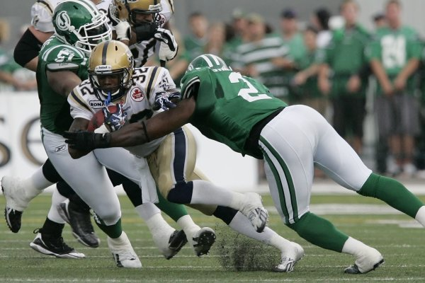 Winnipeg Blue Bombers' Fred Reid (32) is tackled by Saskatchewan Roughriders' Barrin Simpson (2) during the first half of their CFL game in Regina Sun...