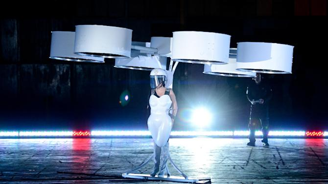 """Lady Gaga demonstrates the Volantis transport prototype """"flying dress"""" designed by TechHaus - Studio XO during the ARTPOP album release and artRave event at the Brooklyn Navy Yard on Sunday, Nov. 10, 2013 in New York City. (Photo by Evan Agostini/Invision/AP)"""