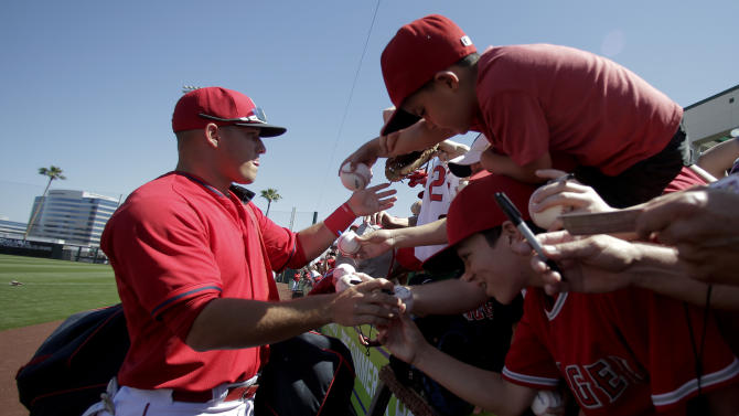 Los Angeles Angels center fielder Mike Trout signs autographs before a spring training baseball exhibition game against the Seattle Mariners in Tempe, Ariz., Monday, March 23, 2015. (AP Photo/Chris Carlson)