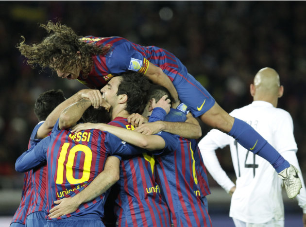 Spain's FC Barcelona defender Carles Puyol, top, celebrates with teammates after Cesc Fabregas (4) scored a goal against Brazil's Santos FC in the first half of their final match at the Club World Cup