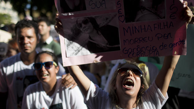 A woman shouts slogans against the city mayor during a protest near the Kiss nightclub where over 230 people died in a fire in Santa Maria, Brazil, Tuesday, Jan. 29, 2013. Santa Maria is a college town of 260,000 people that's been stunned by the early Sunday morning tragedy. (AP Photo/Felipe Dana)