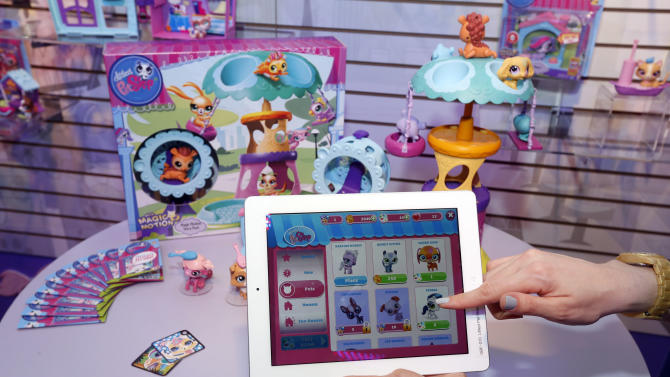 IMADE DISTRIBUTED FOR HASBRO - Demonstrator Chrysten Peddie plays the popular LITTLEST PET SHOP app in Hasbro's showroom at the American International Toy Fair, Sunday, Feb. 10, 2013, in New York.  Currently available for free download on iOS devices, the app allows tweens to take their pet collection with them virtually with an unique Pet Collector token found in each LITTLEST PET SHOP product. (Photo by Jason DeCrow/Invision for Hasbro/AP Images)
