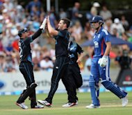 New Zealand's Mitchell McClenaghan (C) and Brendon McCullum (L) celebrate during their ODI against England on Febuary 17, 2013. McClenaghan was unable to complete his final over and limped from the field after delivering a short ball to claim the penultimate wicket when Steven Finn top-edged to Martin Guptill