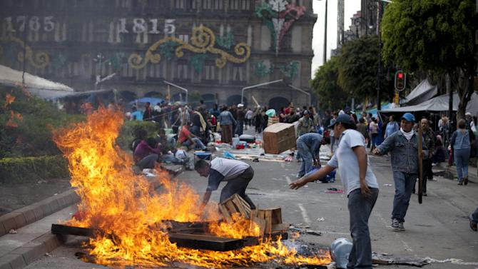 Protesting teachers light a bonfire in Mexico City main plaza, the Zocalo, Friday, Sept. 13, 2013. Thousands of teachers who have camped out at the Zocalo for more than a month have been told by authorities they need to leave today setting the stage for what could be an ugly confrontation culminating weeks of protests against an education reform. As federal police helicopters swooped low overhead Friday, teachers struck tents they have been living in for weeks and burned garbage and plastic traffic barriers, filling the Zocalo with thick, acrid smoke. (AP Photo/Eduardo Verdugo)