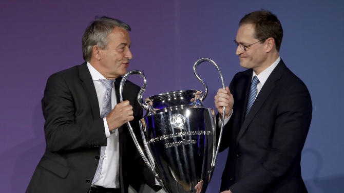 Wolfgang Niersbach, President of the German Soccer Association, left, hands over the Champions League trophy to the Mayor of Berlin, Michael Mueller, right, during a reception in Berlin, Germany, Monday, April 27, 2015. The city of Berlin is host of the Champions League Final 2015. (AP Photo/Michael Sohn)