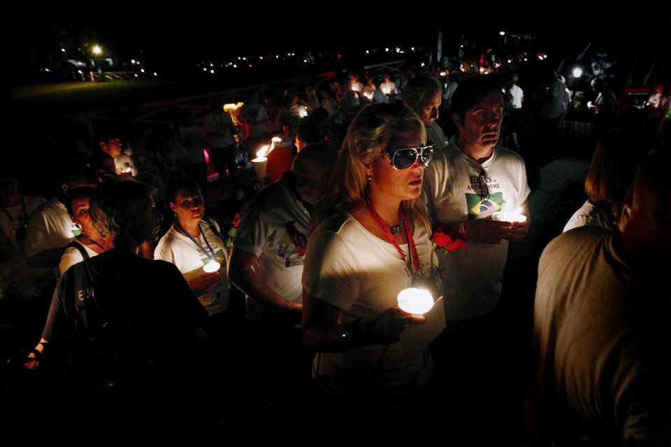 Elvis fan Maria Mendes (middle) lines up with thousand of fans from all over the world as they wait to see the gravesite of Elvis Presley Wednesday Aug. 15, 2012 at Graceland in Memphis, Tenn. during a candlelight vigil marking the 35th anniversary of his death. (AP Photo/The Commercial Appeal, Mark Weber)