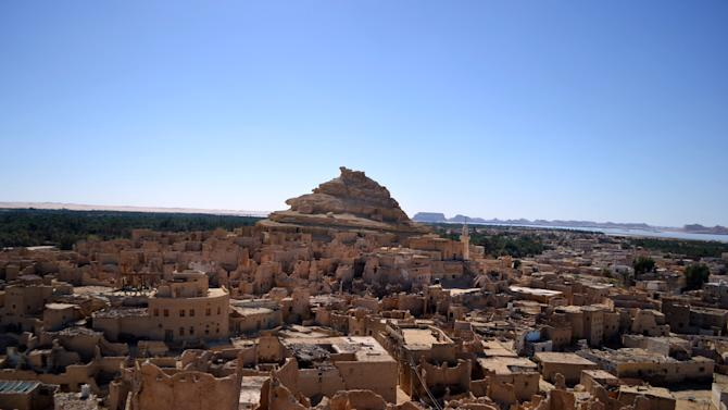 This September 2012 photo shows the labyrinthine Egyptian oasis of Siwa, with the famous Roman-era necropolis known as the Mountain of the Dead in the background, roughly 450 miles (about 725 kilometers) southwest of Cairo. The palm tree-lined area is known for its quiet charm, ancient ruins, abundant natural springs, a vast salt lake and rolling sand dunes in the surrounding desert. (AP Photo/Kim Gamel)
