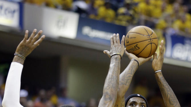 Miami Heat's LeBron James (6) shoots over Indiana Pacers' Paul George (24) during the first half of Game 4 of the NBA basketball Eastern Conference finals, Tuesday, May 28, 2013, in Indianapolis. (AP Photo/Michael Conroy)