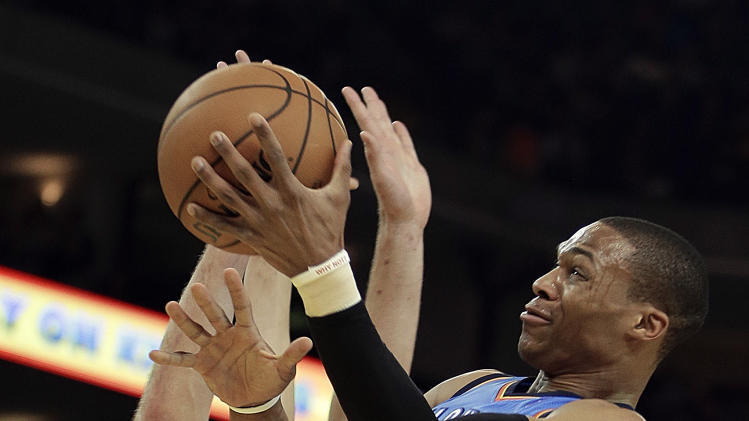 Oklahoma City Thunder's Russell Westbrook, right, lays up a shot against Golden State Warriors' David Lee during the first half of an NBA basketball game, Wednesday, Jan. 23, 2013, in Oakland, Calif. (AP Photo/Ben Margot)