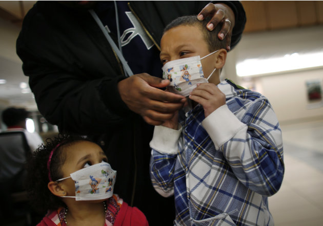 Here Damien Dancy puts masks on his children Damaya, 3, left, and Damien, 7, on Wednesday, Jan. 9, 2013 at Sentara Princess Anne Hospital in Virginia Beach, Va.   Hospitals in Hampton Roads are urging