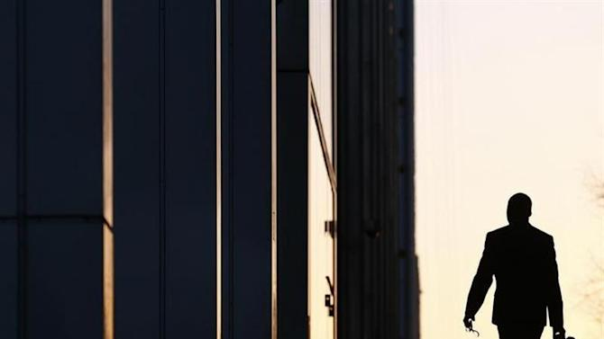 A worker arrives at his office in the Canary Wharf business district in London
