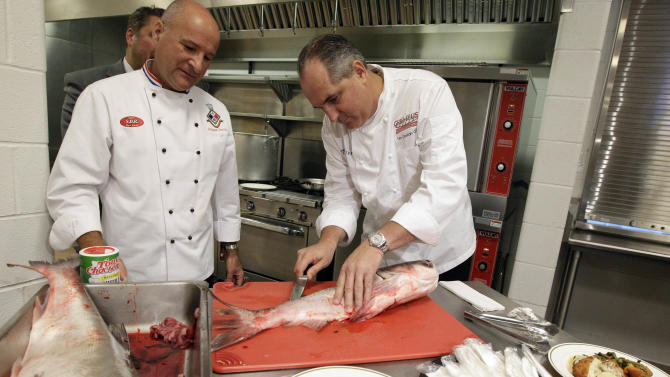 Chef Tim Creehan, right, and chef Philippe Parola prepare food at Christ the King Jesuit College Preparatory High School on Thursday, Sept. 22, 2011, in Chicago. Launch of a campaign by the Illinois Department of Natural Resources to try and change the fish's image and teach people how to cook the ultra-bony meat. (AP Photo/Nam Y. Huh)